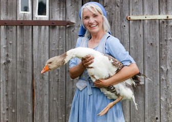 Germany,Bavaria,Mature woman with goose on farm