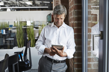 Businessman in office looking at digital tablet
