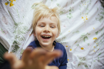 Smiling little boy lying on bed reaching out to camera