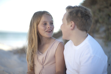 Smiling teenage boy and girl on beach