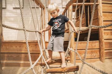 Little boy walking along hanging bridge of wooden ship on playground
