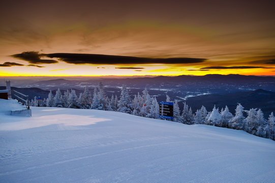 Early morning golden sunrise over groomed ski trails in Vermont,