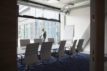 Female manager in conference room looking out of window