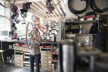 Young woman in a repair shop holding bicycle wheel