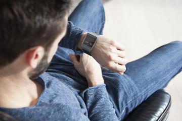 Young man sitting on leather chair looking at his smartwatch