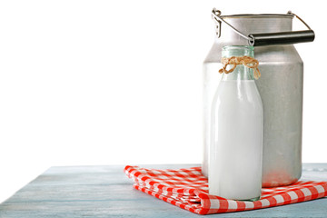 Retro can for milk and glass bottle of milk on wooden table, on white background