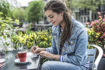 Netherlands, Amsterdam, woman writing postcards in a street cafe