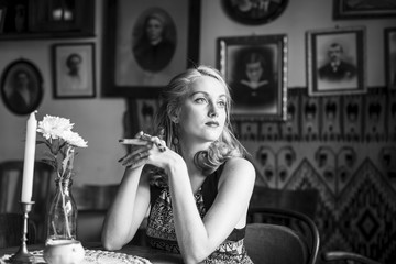 Black and white portrait of a young retro lady sitting at a vintage cafe.