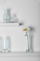 Decorative glass vases with flower  on wooden shelf  on white wallpaper background