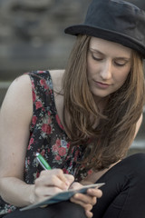 Young woman writing a postcard