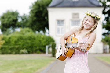 Germany, Holzwickede, portrait of laughing little girl with guitar wearing floral wreath