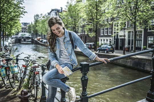 Netherlands, Amsterdam, laughing female tourist with city map in front of town canal