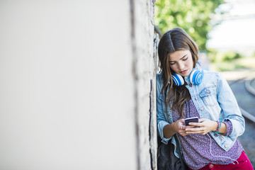 Brunette young woman with headphones and cell phone leaning against wall