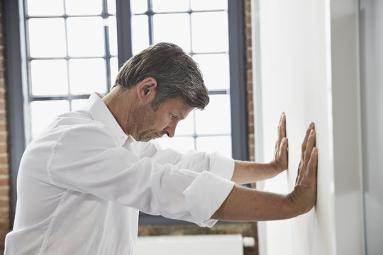 Frustrated businessman in office leaning against a wall