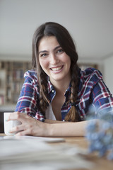 Portrait of smiling young woman with coffee cup relaxing at home