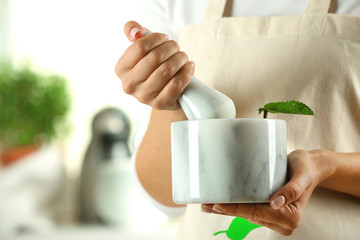 Woman hands with mortar with herbs on bright background