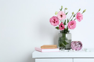 Beautiful flowers with books on wall background