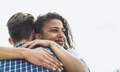 Young woman hugging boyfriend outdoors