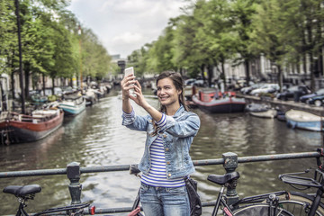 Netherlands, Amsterdam, female tourist taking a selfie with smartphone in front of town canal