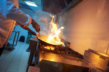 chef in hotel kitchen prepare food with fire