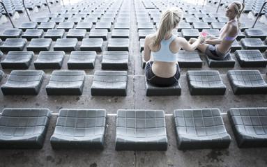 Two sportswomen sitting on grandstand of a stadium