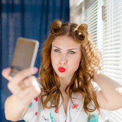 Funny woman taking selfie or selfy photo with smart phone