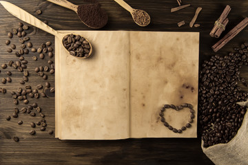 roasted coffee beans on old vintage open book. Menu, recipe, mock up. Wooden background.