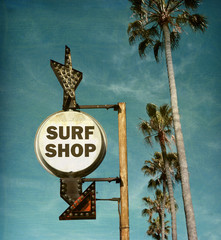 aged and worn vintage photo of surf shop sign on beach with palm trees