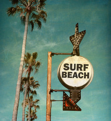 aged and worn vintage photo of surf beach sign with palm trees
