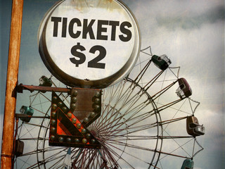 aged and worn vintage photo of ticket sign at carnival with ferris wheel