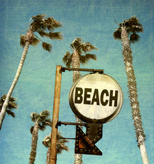 aged and worn vintage photo of beach sign with arrow and palm trees