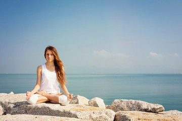 Beautiful young woman practicing yoga and relax in lotus pose at seashore