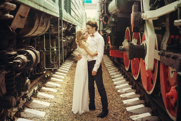 Beautiful Bride in Wedding Dress and Groom Just Married Kissing near Trains on Railroad. Honeymoon Travel