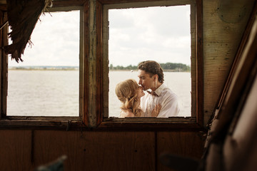 Beautiful Love Wedding Couple Kissing Outside the Window of Old Ship