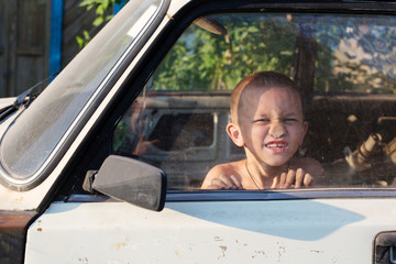 Funny Boy Behind Glass in Old Car Playing Outdoor