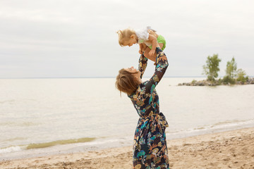 Young Mother and her Little Daughter Baby Outdoor Playing on the Beach near Sea. Family Love Concept