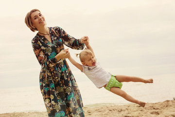 Mother and Little Baby Daughter having Fun and Playing on the Beach