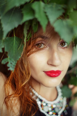 Portrait of Beautiful Young Woman in Nature with Red Lips and Leaves on Head