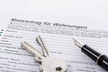 Mietvertrag, Wohnungsschlüssel und Federhalter zum Unterschreiben