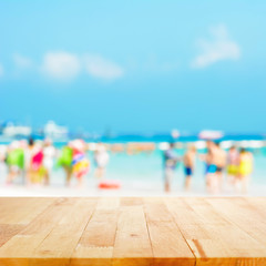 Wood table top on blurred beach background with people in colorful clothes