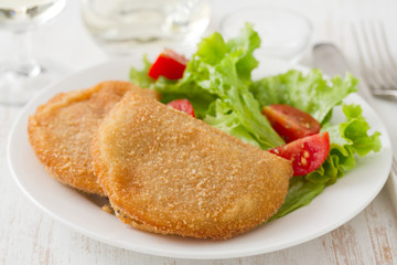 portuguese meat cookies with fresh salad on white dish on white wooden background