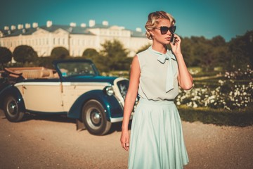 Beautiful lady with mobile phone near classic convertible