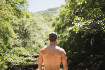 Back of a shirtless man with peaked cap
