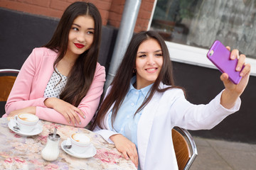 Happy Young asian women making selfie photo on smartphone