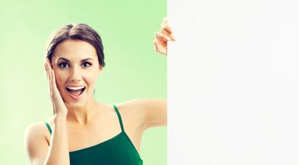 Woman in fitnesswear showing signboard, on green