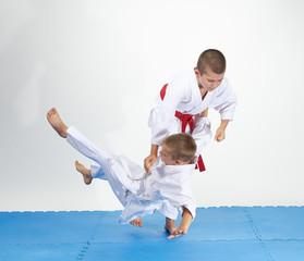 In white judogi athletes train judo throws