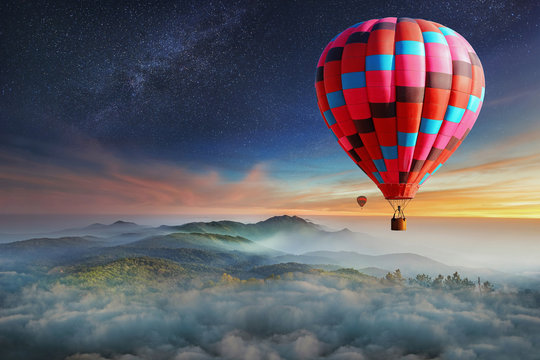 Colorful hot-air balloons flying over the mountain with with stars. Beautiful mountains landscape with clouds at sunset
