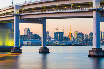 The twilight of Rainbow Bridge at night with Tokyo Tower in Japa