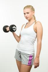 Hübsche junge blonde Frau trainiert mit einer Hantel