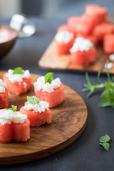 Summer appetizer of heart-shaped watermelon with feta cheese and rosemary or mint leaves. Selective focus